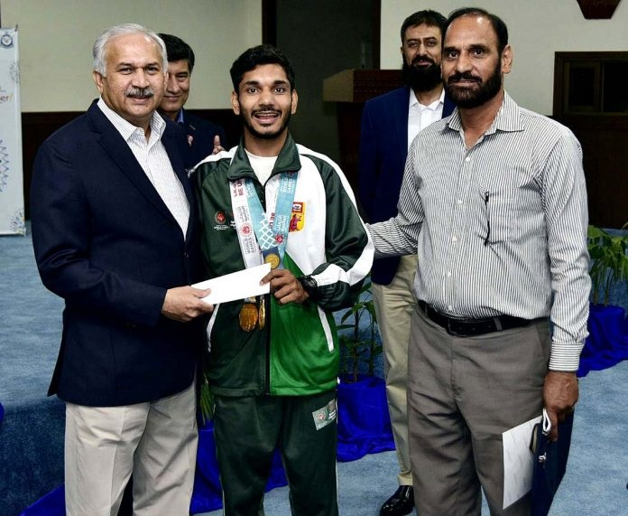 Air Chief Marshal Mujahid Anwar Khan, Chief of the Air Staff, Pakistan Air Force awarding cash prize to Imran Ghaffar who won 02 Gold Medals in Cycling in Special Olympics 2019 held at Abu Dhabi.